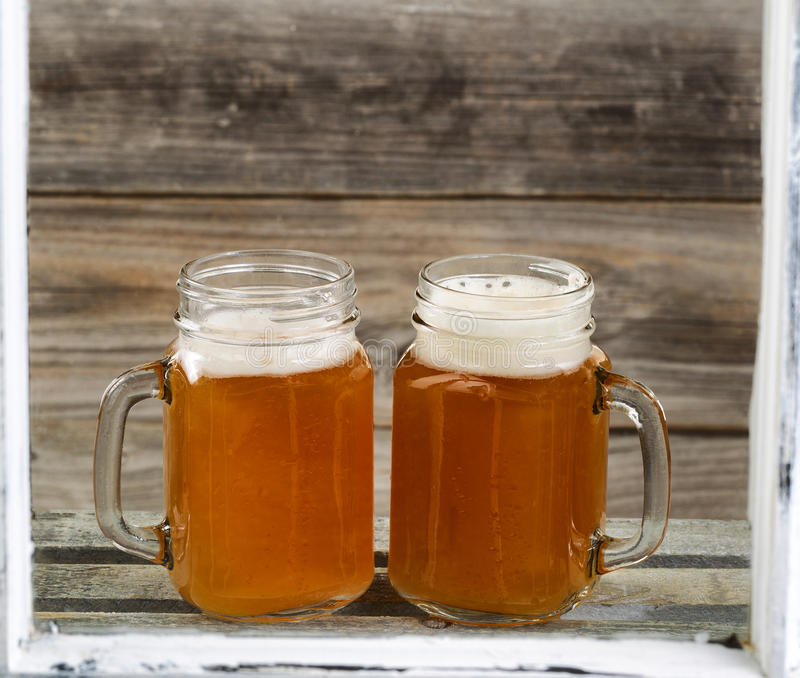 Window view of two pints of fresh cold beer on top of wooden crate with rustic wood in background. View through windows of two glass jars filled with frosty cold royalty free stock photos