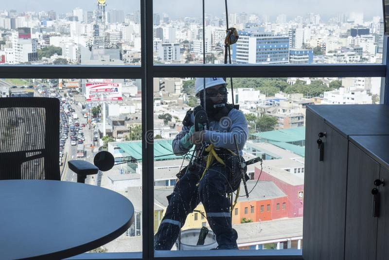 Window washers cleaning the glass facade of a modern building, high risk work. stock photography