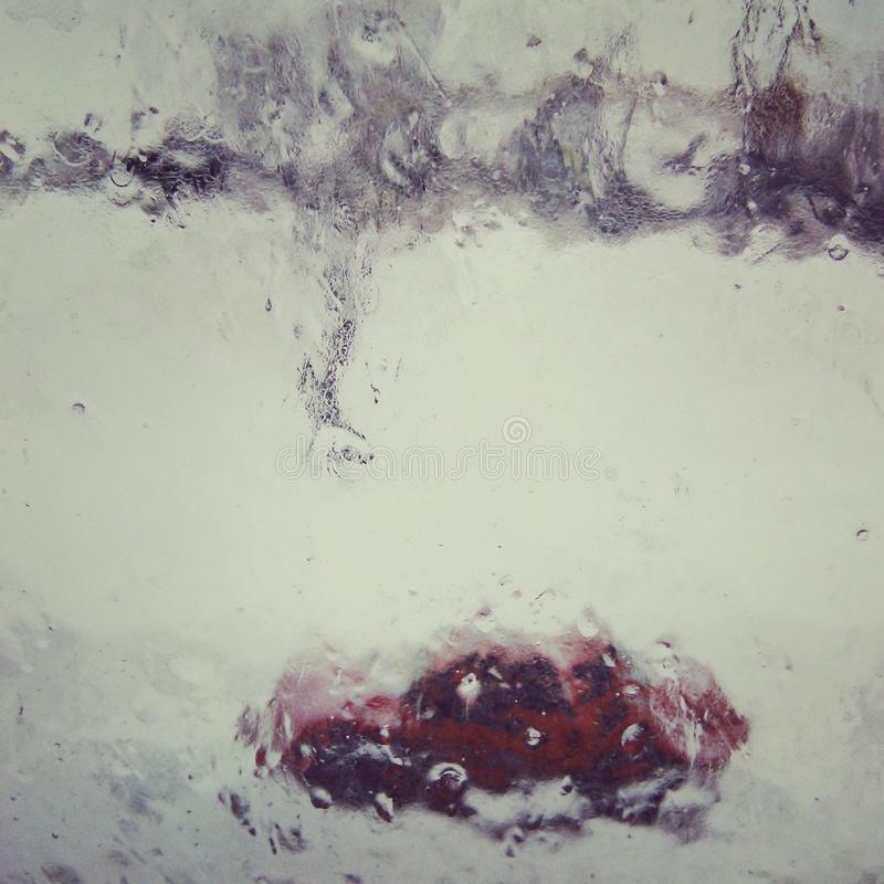 The window which has iced over on wind. On a frost the drizzle began and through the rimed window the silhouette of the red car which seems drawn as in a picture stock image