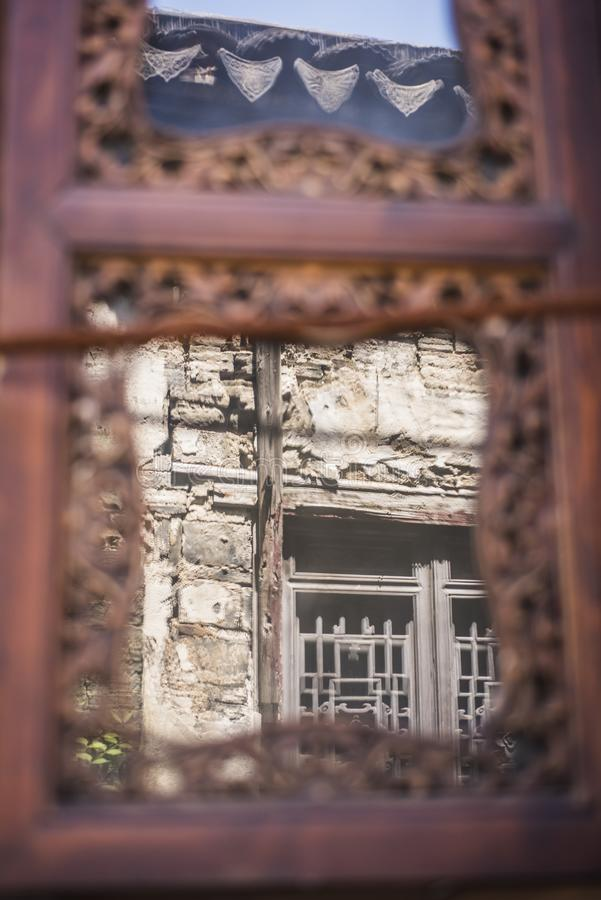 Window in the window. An old wooden window reflects the Windows of another house, creating Windows in the old gate east of the qinhuai district of nanjing