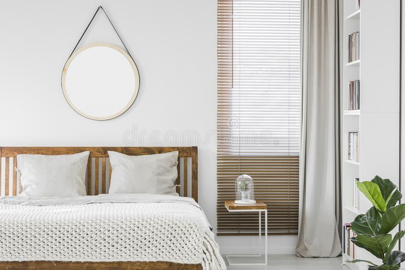 Window with wooden blinds and light grey curtain in white bedroom interior with mockup poster, double bed and rack with books. Window with wooden blinds and stock photography