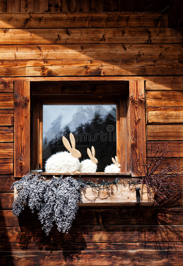 Window on wooden house, decorations and rabbit shapes royalty free stock photos