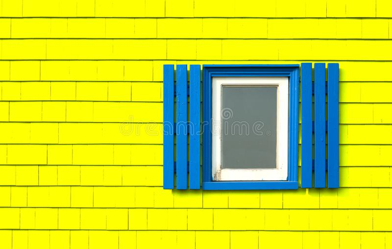 Window on yellow wooden wall. Traditional window with blue shutters on a bright yellow wooden tiles wall in Iles de la Madeleine in Quebec, Canada stock images
