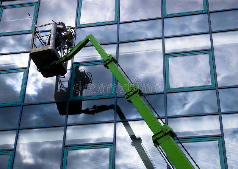 Windowclean. Window cleaner working on a glass facade in a gondola royalty free stock photo