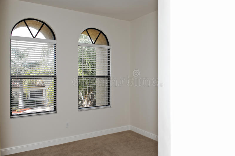 Windowed room. Looking into empty room that has two arched windows with copy space on nearest wall stock photo