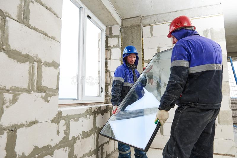 Windows设施 安装玻璃的两名建筑工人 免版税库存图片