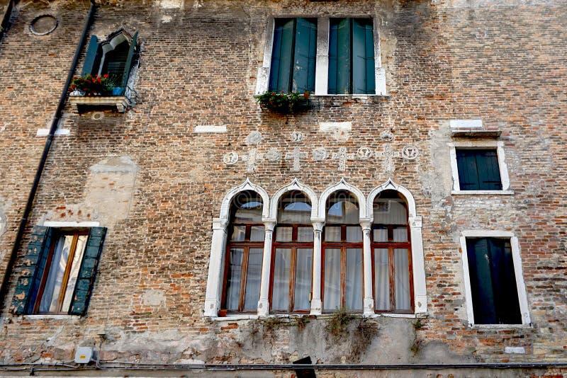 Windows смешало на здании кирпичной стены стоковые изображения