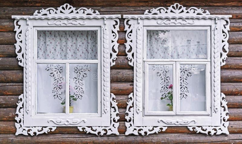 Windows с белыми высекаенными рамками в старом деревянном доме стоковая фотография