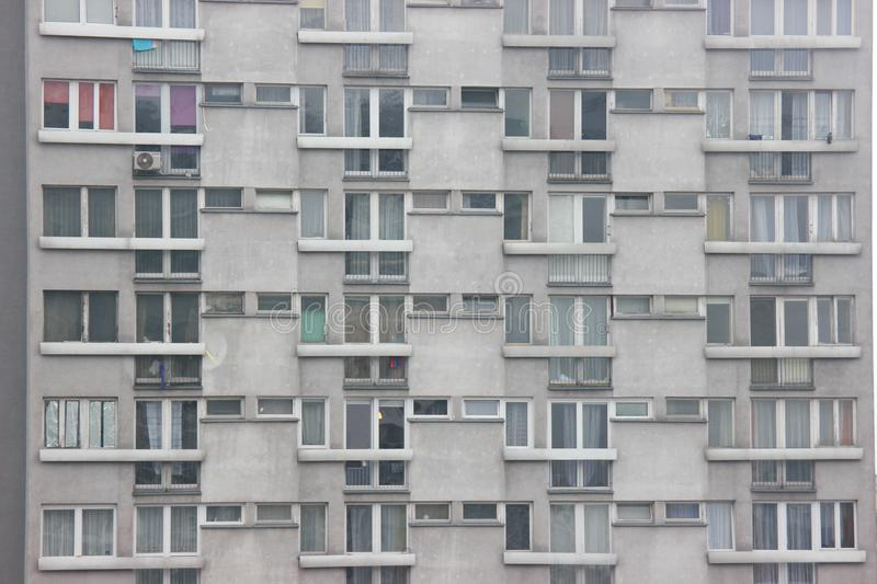 Windows of an apartment building, symmetrical frames in a gray house. many rooms in one house. modern housing construction. Windows of apartment building stock photo