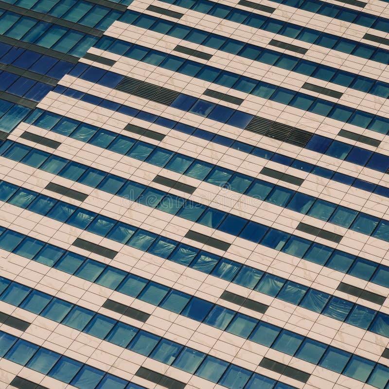 Windows av under-konstruktionshöghus Främre sikt av modern exponeringsglas- och betongyttersida av hög löneförhöjningbyggnad royaltyfri foto