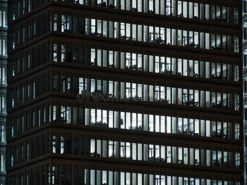 Windows av vit tände kontor i högväxt kontorsbyggnad royaltyfri foto