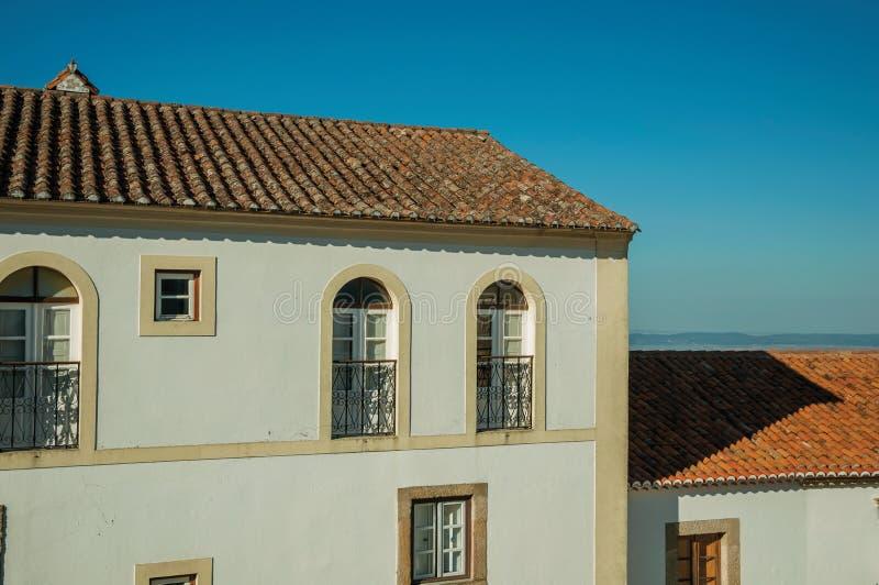 Windows avec la rampe et le toit de fer travaillé dans une vieille façade de maison photos libres de droits