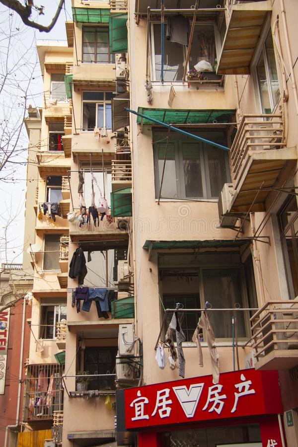 Windows and balconies on residential buildings with clothes hanging at windows in rural modern China. royalty free stock image