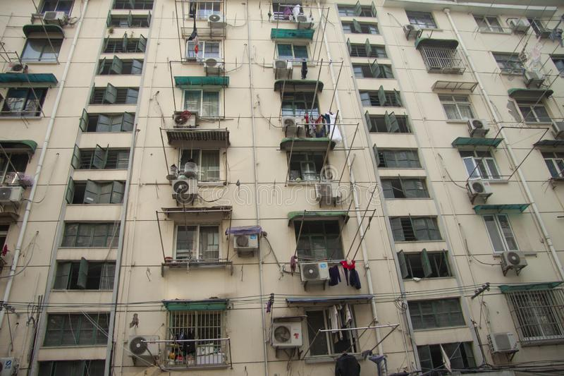 Windows and balconies of residential buildings with lots of air conditioning and clothes hanging at windows in rural modern Beijin royalty free stock image