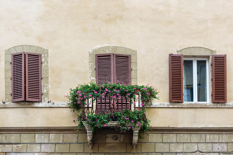 Windows and balcony with wooden shutters of old house in Siena. Italy. Traditional windows and balcony with wooden shutters of old house in Siena. Italy royalty free stock photo