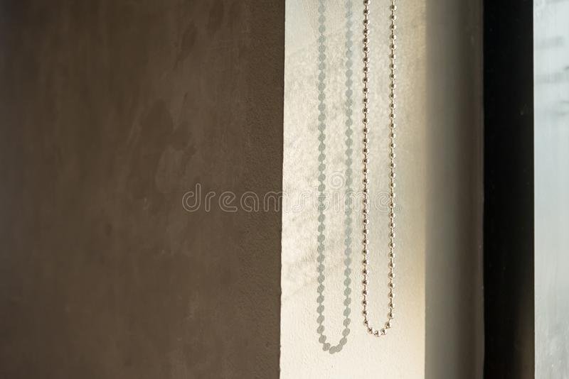 Windows blinds chain, glass and sun light. stock images