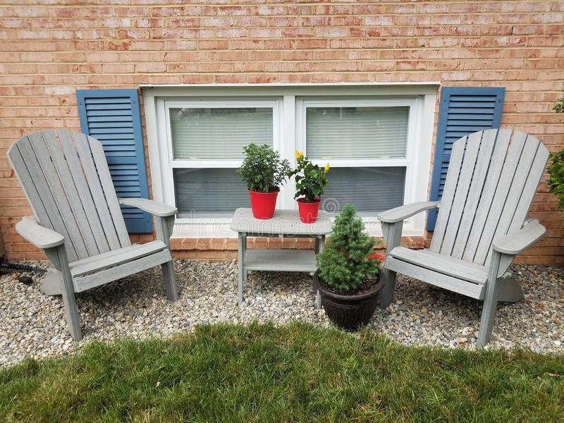 Windows and blue shutters and chairs and plants and rocks stock image
