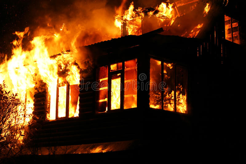 Windows of the burning house. The burning house at night. The flame takes off from windows stock images