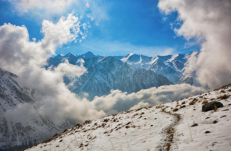 Windows of clouds in mountains. Beautiful misty rock landscape with snow and clouds stock images