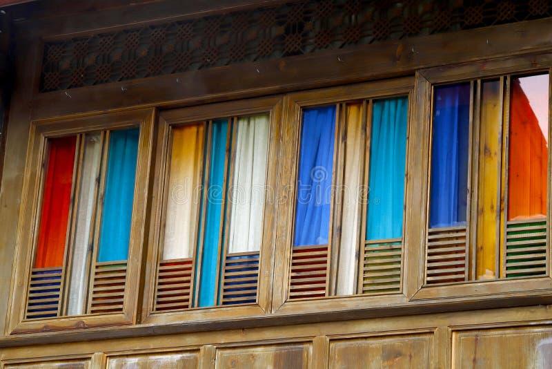 Windows com as cortinas de várias cores, Lijiang, Yunnan, China foto de stock