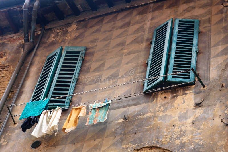 Windows con los obturadores de madera de la casa vieja en Siena Italia foto de archivo libre de regalías