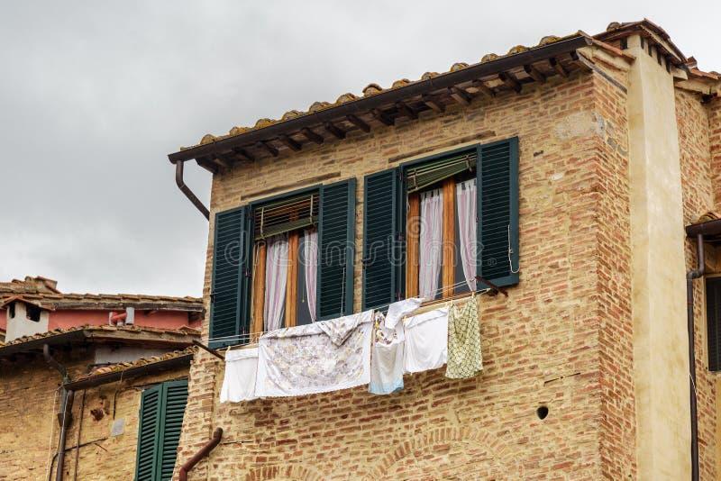 Windows con los obturadores de madera de la casa vieja en Siena Italia imagenes de archivo