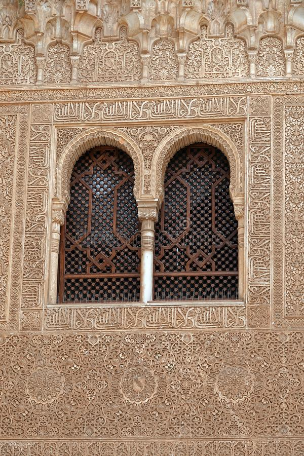 Window in Comares palace at the Alhambra in Granada, Andalusia. Windows decorated with arabesque ornaments in the Comares Palacio at the Court of the Myrtles of stock image