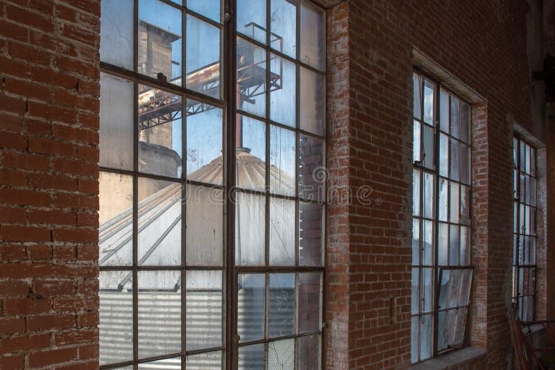 Windows in der alten Fabrik mit Wand des roten Backsteins stockfotos