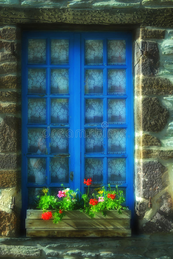 Window on stone built house. A window with blue frames on a French stone built house and a box with flowers royalty free stock photos