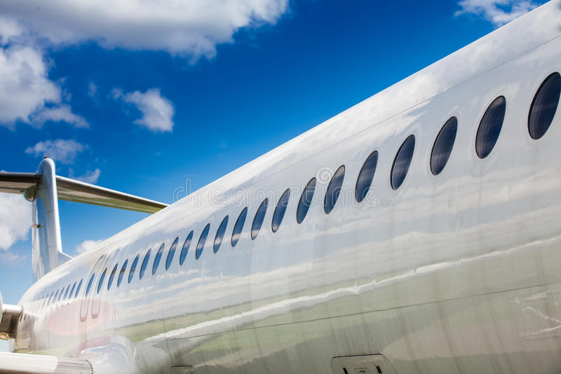 Windows and fuselage of a private airplane. With tail against the cloudy sky royalty free stock images