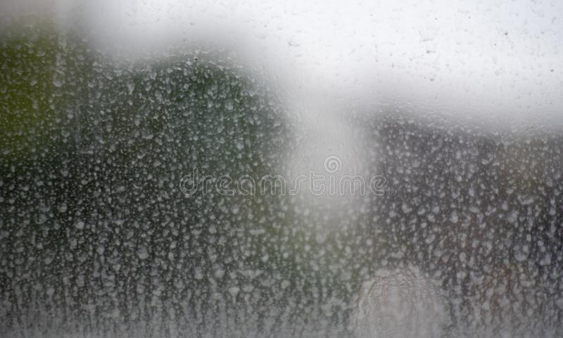 Windows glass with with dust mix with rain. Material, dusty, contrasts, droplets, dirty, abstract, surface, smudged, stain, greasy, grime, refraction, streak royalty free stock image