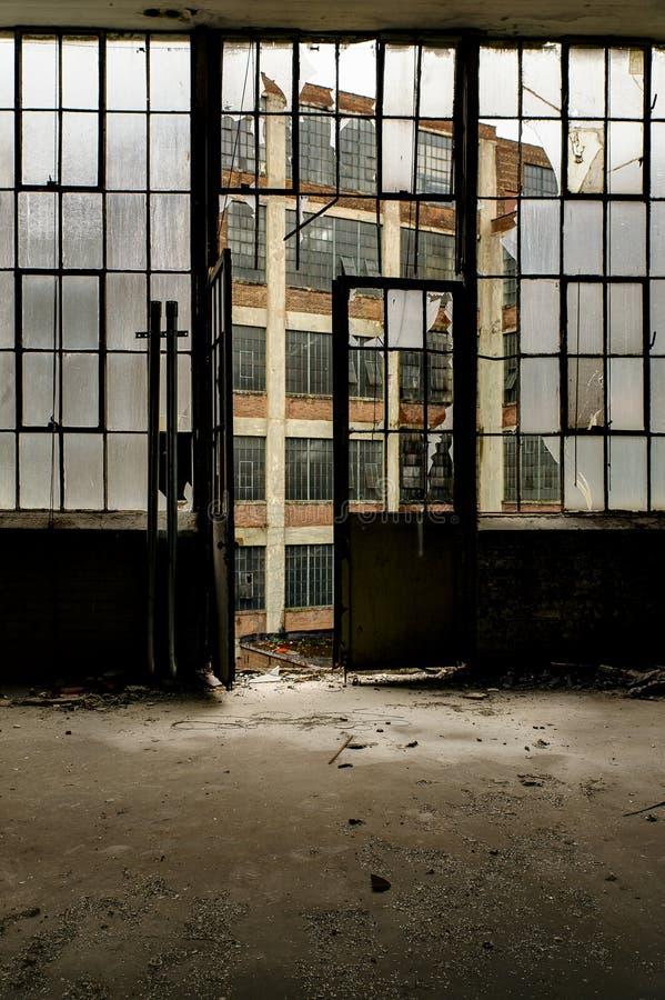 Windows grande y puerta que miran hacia fuera - la fábrica abandonada de la ropa fotografía de archivo