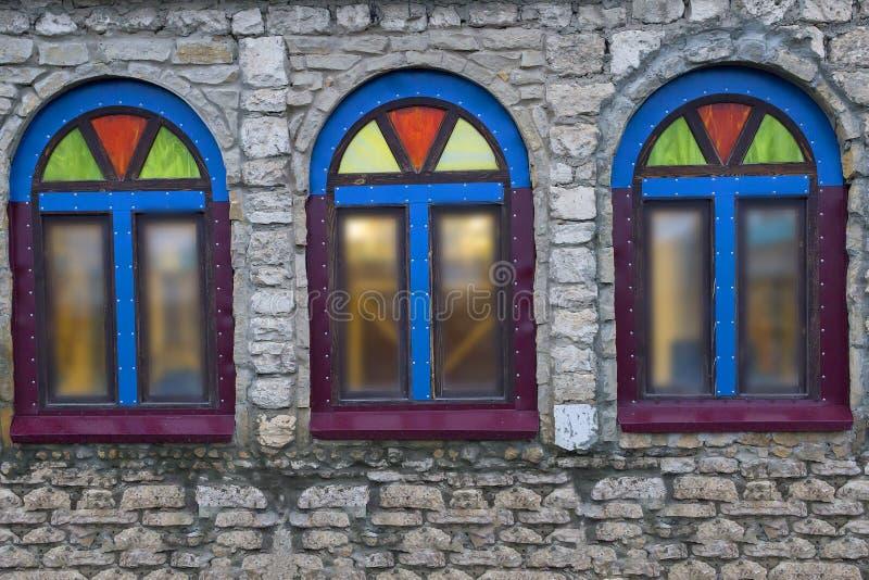 Windows i en stenbyggnad med färgat exponeringsglas royaltyfria foton