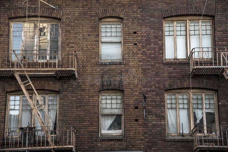 Windows i pożarniczych ucieczek tenement cegły budynek mieszkaniowy obraz stock