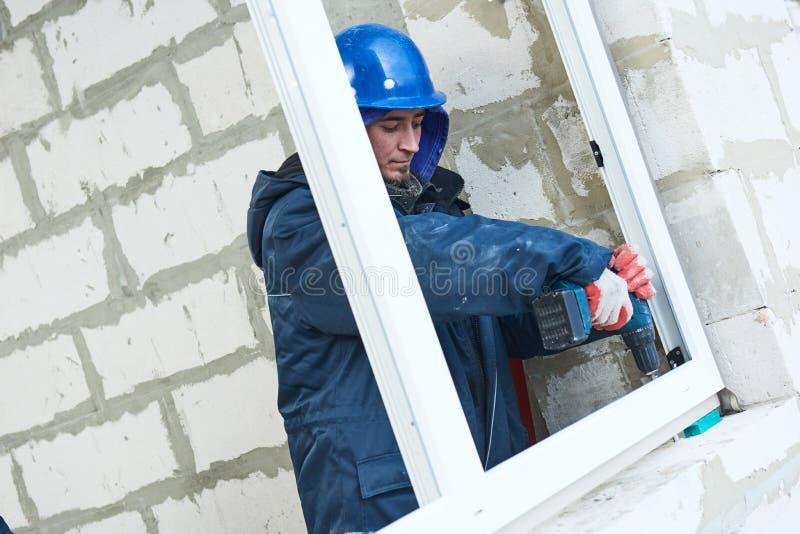 Windows instalacja pracownicy budowlani instaluje ramę w aperturę fotografia stock