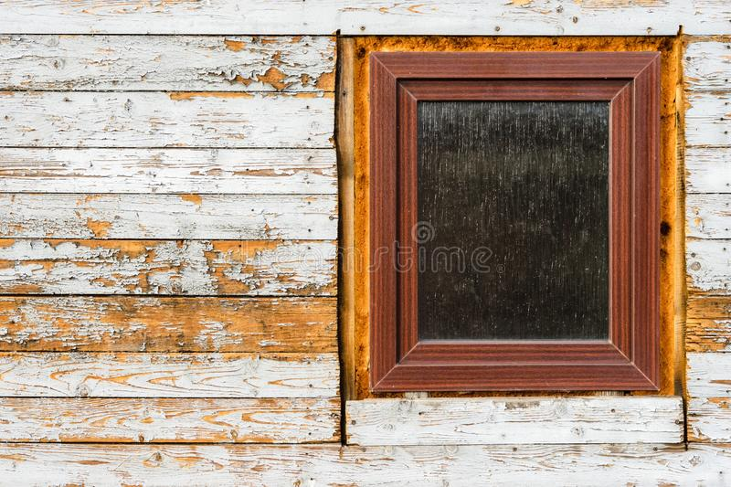 Windows installed in old wooden house, peeling paint on wooden planks, wearing texture. Windows installed in old wooden house, peeling paint on wooden planks stock photos