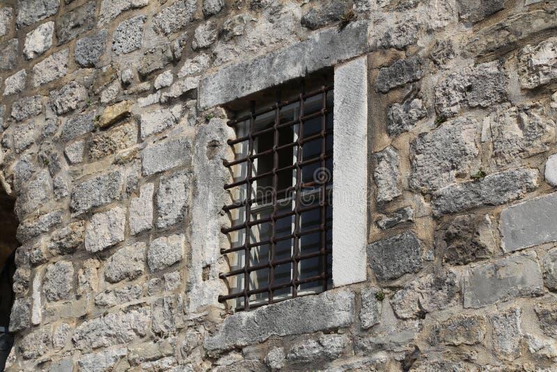 Windows med metallskyddsgallrar, sikt från gatan royaltyfria foton