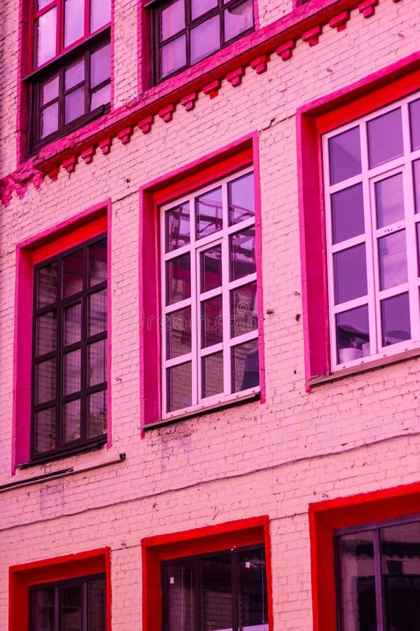 Windows med röda ramar i enbostads- byggnad royaltyfria foton