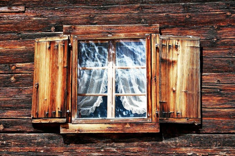 Windows mit Vorhängen und Fensterläden auf einem alten Holzhaus stockfotos