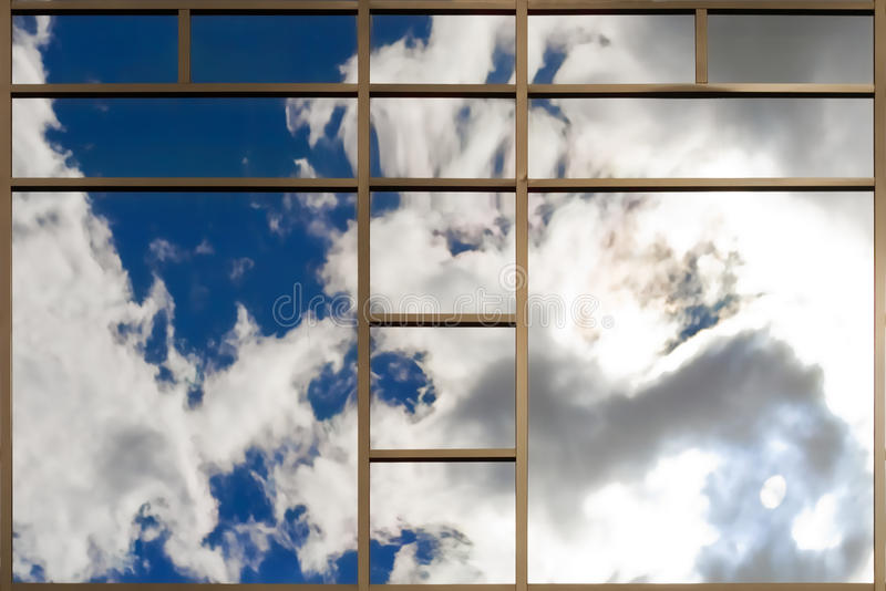 Windows of modern office building. Clouds reflected in windows of modern office building royalty free stock images