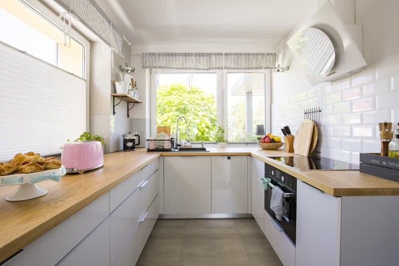 Windows nell'interno bianco della cucina con i gabinetti grigi e di legno fotografie stock