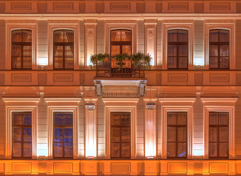 Windows on night facade of Kempinski Hotel Moika 22. Several windows and balcony in a row on night illuminated facade of the Kempinski Hotel Moika 22 front view royalty free stock photos