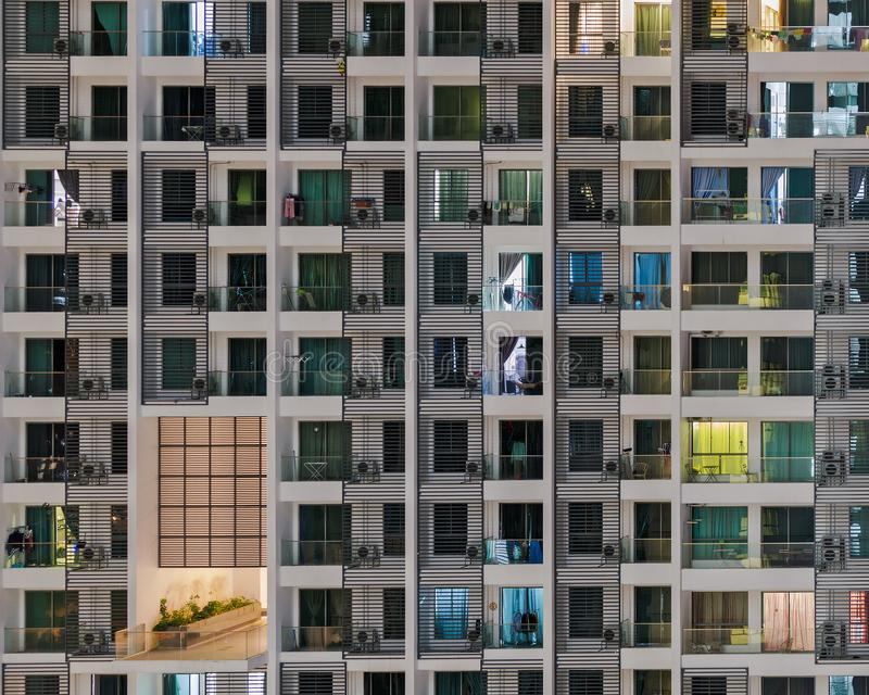 Windows at night. Sleeping building. Frontal view of facade of residential building with a lot of illuminated windows royalty free stock image
