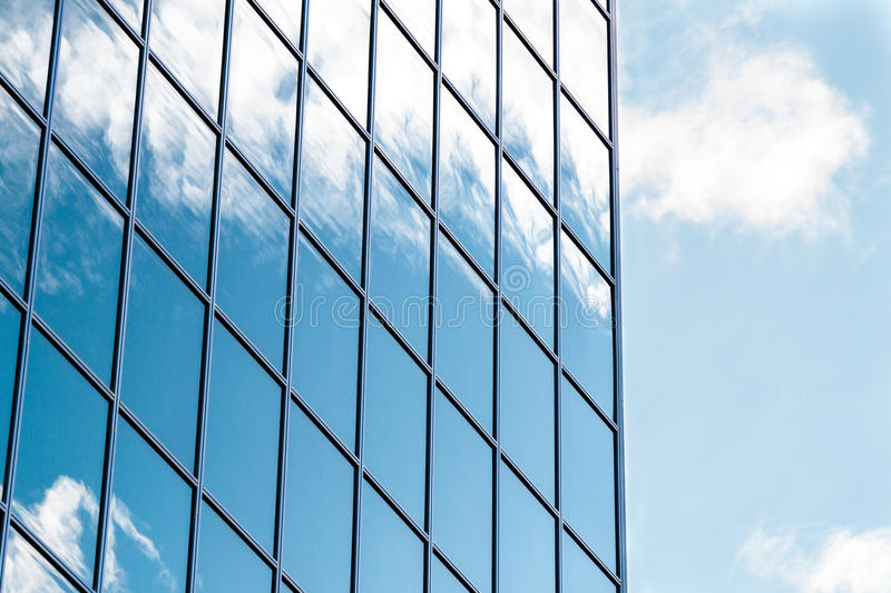 Windows of the office building. Clouds reflected in windows of modern office building stock images