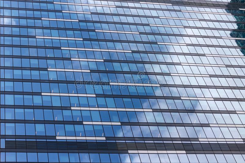 Windows of an office building with reflection of sky and clouds royalty free stock photo