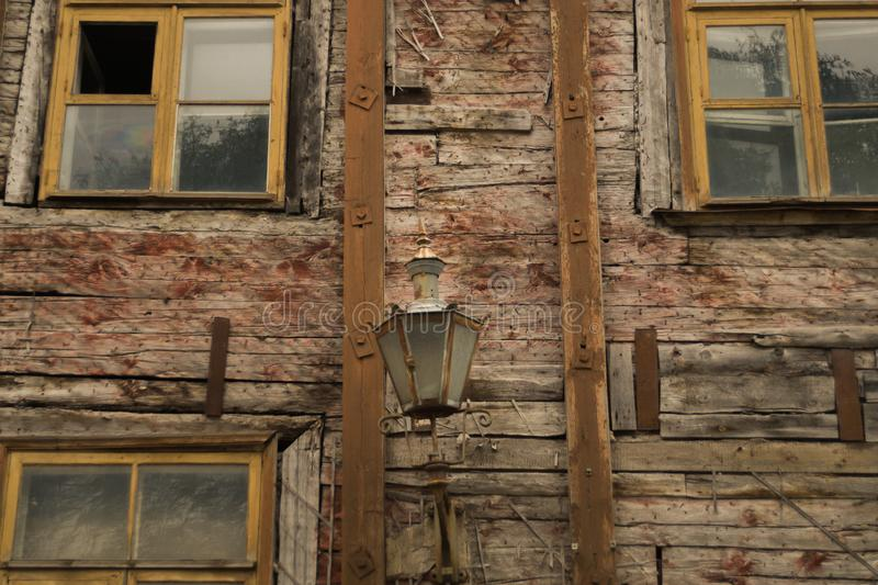 Windows of the old wooden house. wooden wall with windows and vintage lamp stock photos
