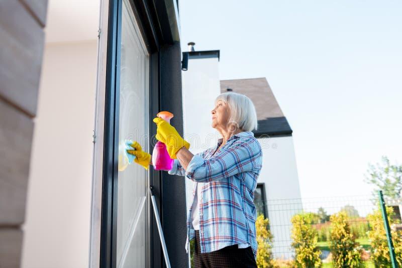 Elderly housewife wearing blue squared shirt washing windows outside stock image