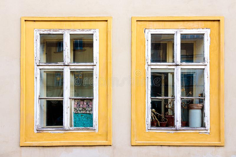 Colorful window frames, Prague, Czech Republic. Windows painted with yellow on white wall outside home in Prague, Czech Republic stock images