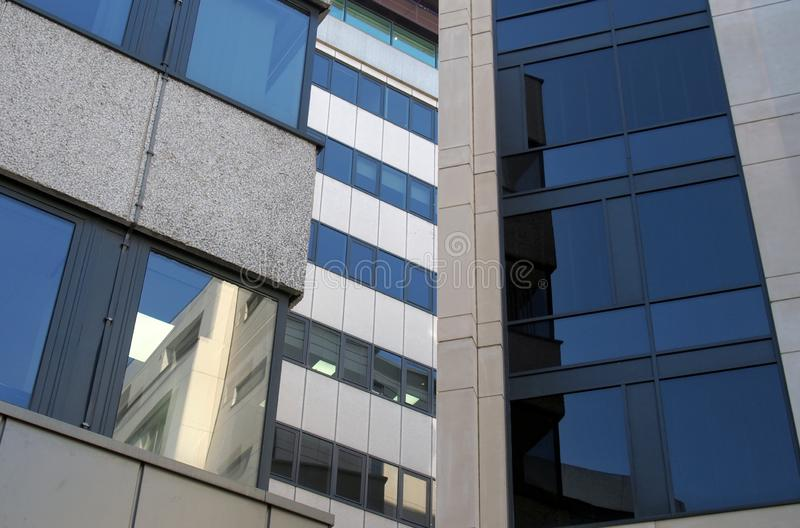 Reflections in the windows of a group of large modern office buildings in a city business district. Reflections in the windows of a group of large modern royalty free stock images