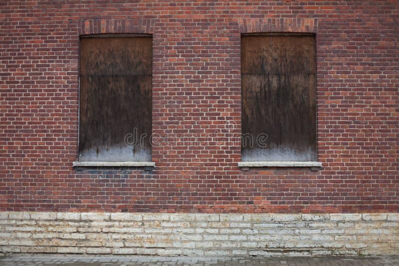 Windows s'est fermé fermé sur une maison rouge foncé de brique photographie stock